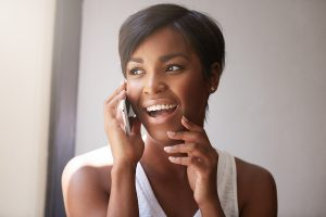 Young attractive African woman with short haircut talking on cell phone to her friend looking cheerful joyful and happy sitting at the window touching her chin. Human emotions and feelings